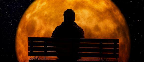 Sedí na lavičce a dívá se na měsíc